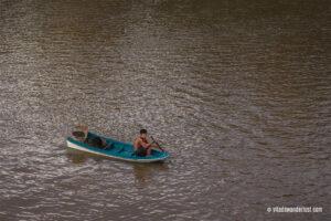 Un bambino in canoa in attesa che gli venga regalato qualcosa